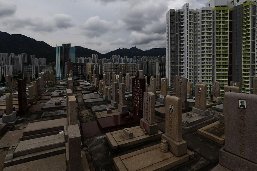 Headstones stand at a cemetery surrounded by residential flats in downtown Hong Kong on May 29, 2014. -- PHOTO: REUTERS