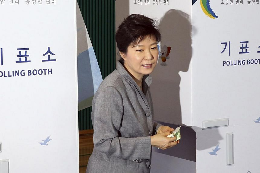 South Korean President Park Geun-hye walks out a voting booth after marking her ballots for the local elections at a polling station in Seoul on June 4, 2014. Exit polls in South Korean local elections on Wednesday, June 4, 2014, signalled the t