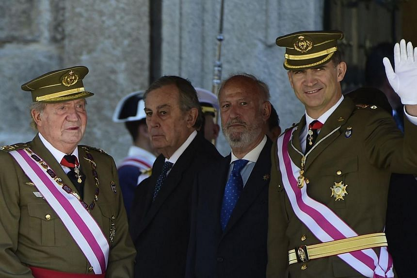 Spanish King Juan Carlos (L) and Spain's Crown Prince Felipe stand during a military ceremony marking the bicentenial of the Royal and Military Order of Saint Hermenegild (Real y Militar Orden de San Hermenegildo) in El Escorial on Jun 3, 2014. Spain