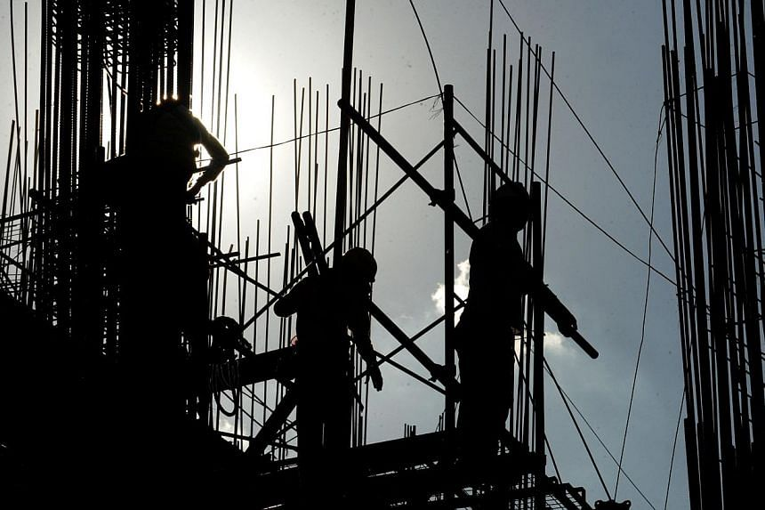 Labourers are silhouetted as they work on a building construction site in suburban Manila on April 1, 2014. Construction can be all around the metropolis: condominiums, office buildings, highways, airports, interchanges. Butwho's getting the li