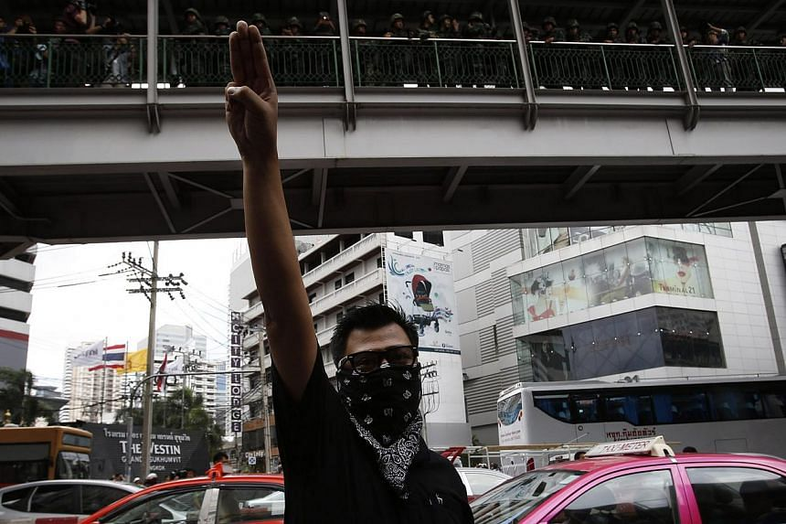 A protester against military rule gestures by holding up his three middle fingers in the air, as soldiers look on from an elevated walkway, during a brief demonstration outside a shopping mall in Bangkok June 1, 2014. -- PHOTO: REUTERS
