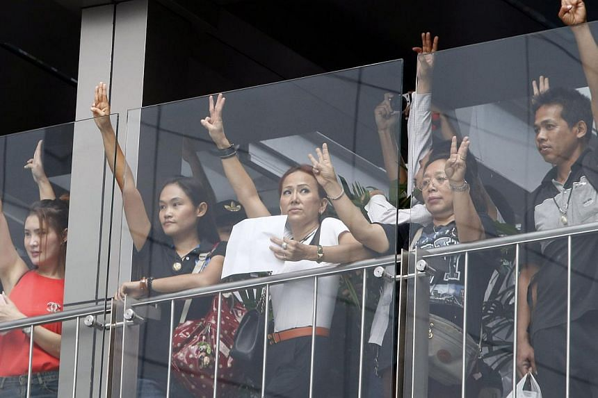 Protesters against military rule gesture by holding up their three middle fingers in the air, during a brief demonstration at a shopping mall in Bangkok June 1, 2014. -- PHOTO: REUTERS
