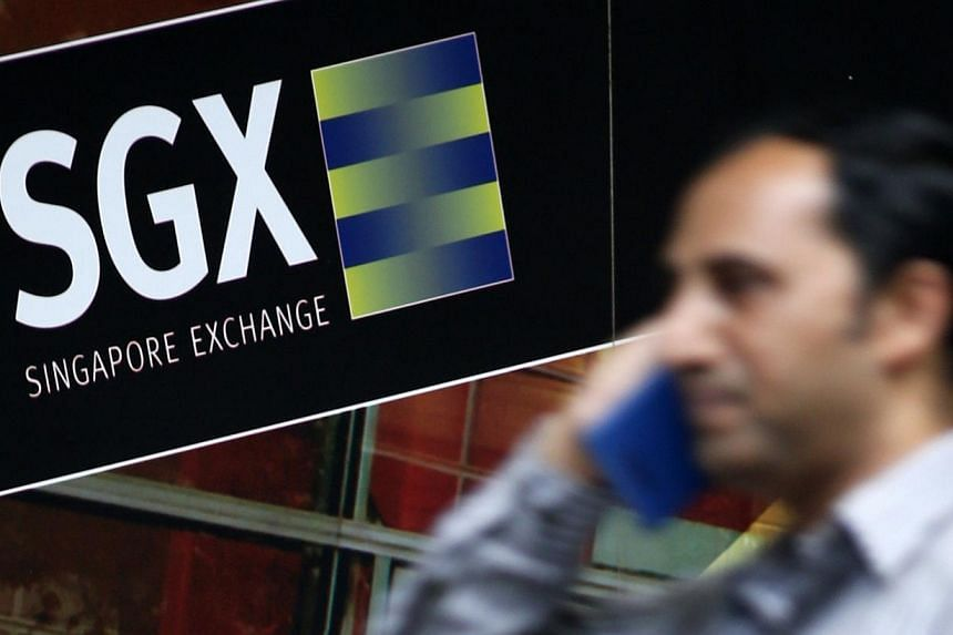 An office worker walks past a logo of the Singapore Stock Exchange (SGX) on April 23, 2014. -- PHOTO: REUTERS