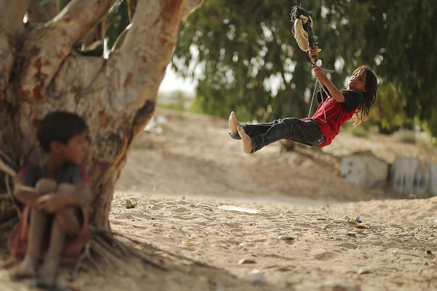 A Palestinian girl swings on a rope tied on a tree at a former Jewish settlement in Khan Younis in the southern Gaza Strip June 3, 2014. -- PHOTO: REUTERS