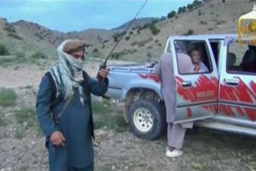 A Taliban militant speaks to U.S. Army Sergeant Bowe Bergdahl (right) waiting in a pick-up truck before his release at the Afghan border, in this still image from video released on June 4, 2014. -- PHOTO: REUTERS