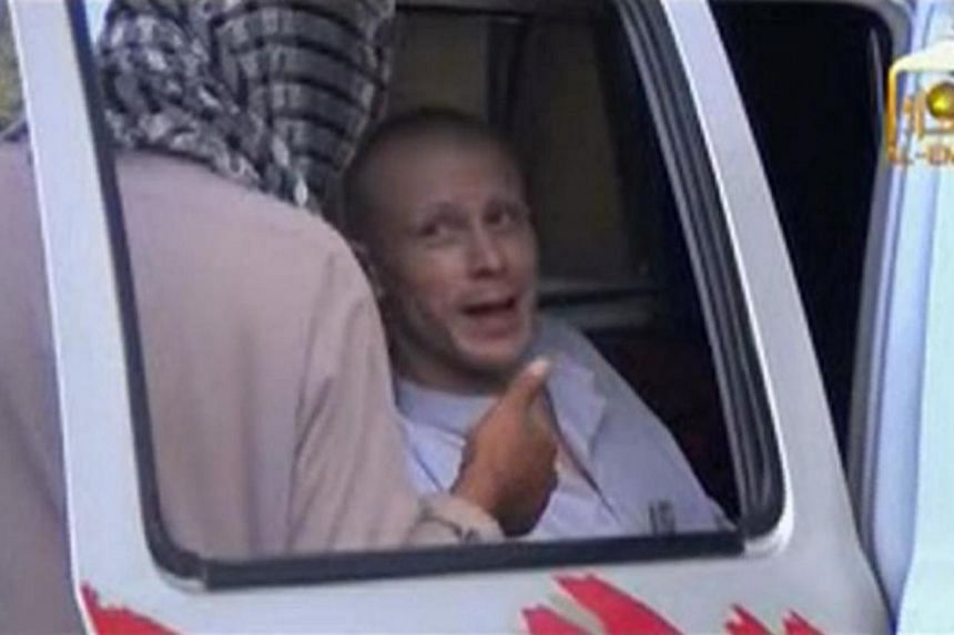 U.S. Army Sergeant Bowe Bergdahl (right) talks to a Taliban militant as he waits in a pick-up truck before his release at the Afghan border, in this still image from video released on June 4, 2014.-- PHOTO: REUTERS