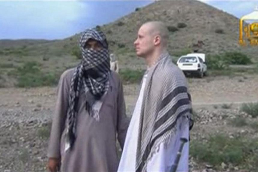 U.S. Army Sergeant Bowe Bergdahl (right) waits before being released at the Afghan border, in this still image from video released on June 4, 2014.-- PHOTO: REUTERS
