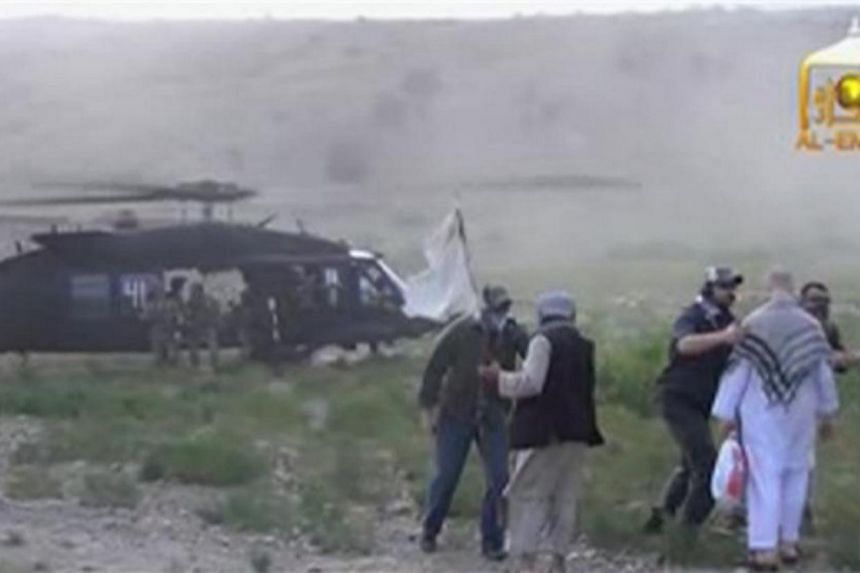 A Blackhawk helicopter waits as U.S. Army Sergeant Bowe Bergdahl (2nd right, back facing) is being led to the American military during his release at the Afghan border, in this still image from video released on June 4, 2014.-- PHOTO: REUTERS