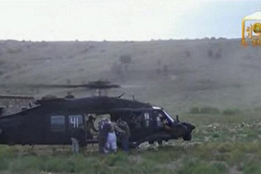 U.S. Army Sergeant Bowe Bergdahl (2nd right, back facing) is led to a waiting Blackhawk helicopter during his release at the Afghan border, in this still image from video released on June 4, 2014. -- PHOTO: REUTERS