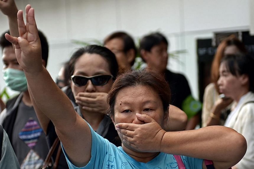An anti-coup protester flashing the three-finger salute borrowed from the Hunger Games movies during a gathering at a shopping mall, which was broken up by security forces of Thailand's ruling junta. -- PHOTO: AFP