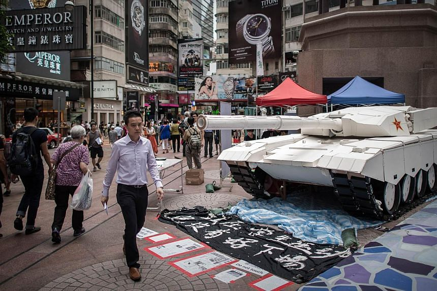 Pedestrians walk past a tank replica displayed to symbolise China's June 4, 1989 Tiananmen military crackdown in Hong Kong on June 3, 2014. -- PHOTO: AFP