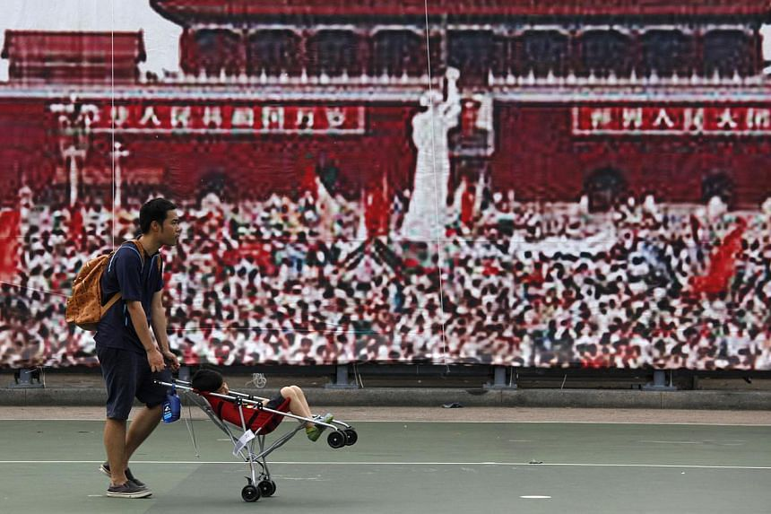 A man and his child pass by a backdrop showing a pro-democracy movement at Beijing's Tiananmen Square in 1989, at Hong Kong's Victoria Park on June 3, 2014. -- PHOTO: REUTERS