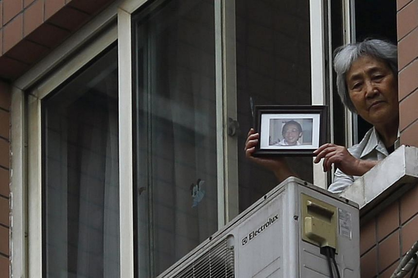 Zhang Xianling, whose son Wang Nan was killed by soldiers at the Tiananmen Square in 1989, holds his picture after journalists were turned away, at the window of her home in Beijing, on April 24, 2014. -- PHOTO: REUTERS
