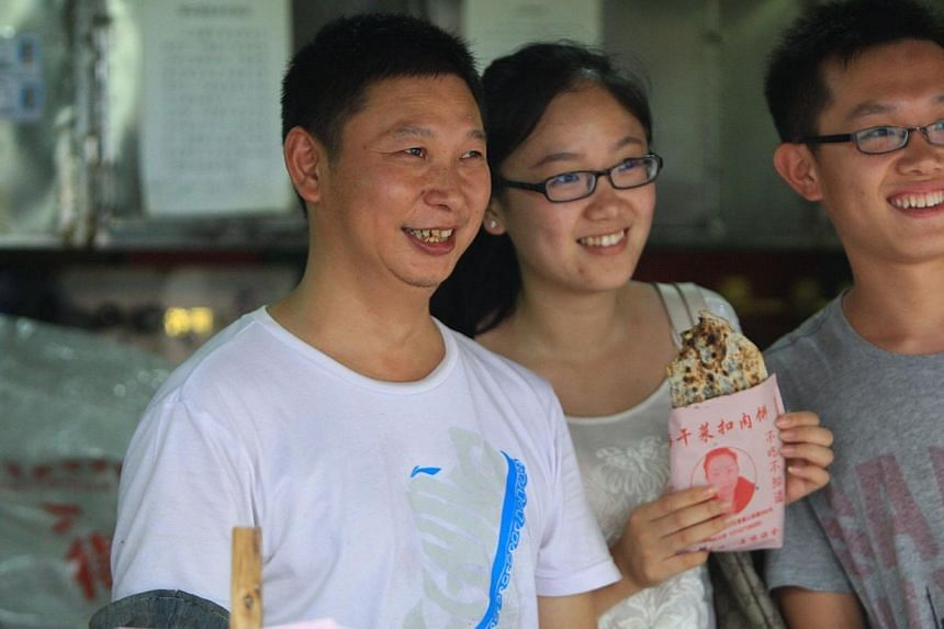 Meat-pie vendor Shao Jianhua (left), who looks like Chinese President Xi Jinping, poses for a photo with customers at his stall in Changsha, central China's Hunan province on June 5, 2014. -- PHOTO: AFP