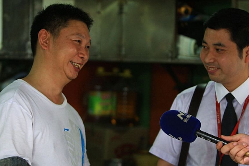 Meat-pie vendor Shao Jianhua (left), who looks like Chinese President Xi Jinping, is interviewed at his stall in Changsha, central China's Hunan province on June 5, 2014. -- PHOTO: AFP