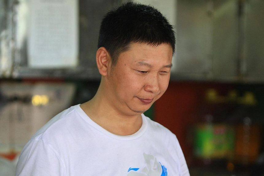 Meat-pie vendor Shao Jianhua, who looks like Chinese President Xi Jinping, works at his stall in Changsha, central China's Hunan province on June 5, 2014. -- PHOTO: AFP