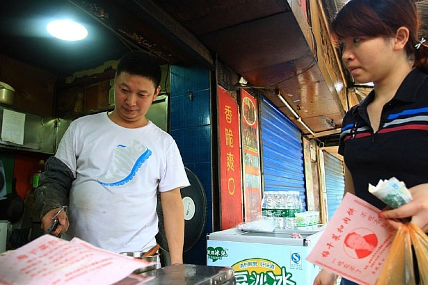 Meat-pie vendor Shao Jianhua (left), who looks like Chinese President Xi Jinping, works at his stall in Changsha, central China's Hunan province on June 5, 2014. -- PHOTO: AFP