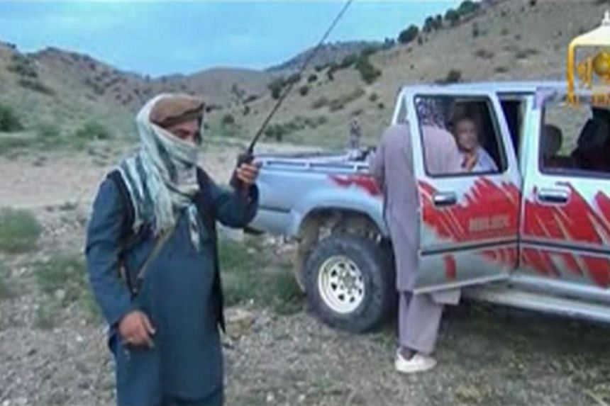 A Taliban militant speaks to U.S. Army Sergeant Bowe Bergdahl (right) waiting in a pick-up truck before his release at the Afghan border, in this still image from video released on June 4, 2014. US President Barack Obama on Thursday, June 5, 20