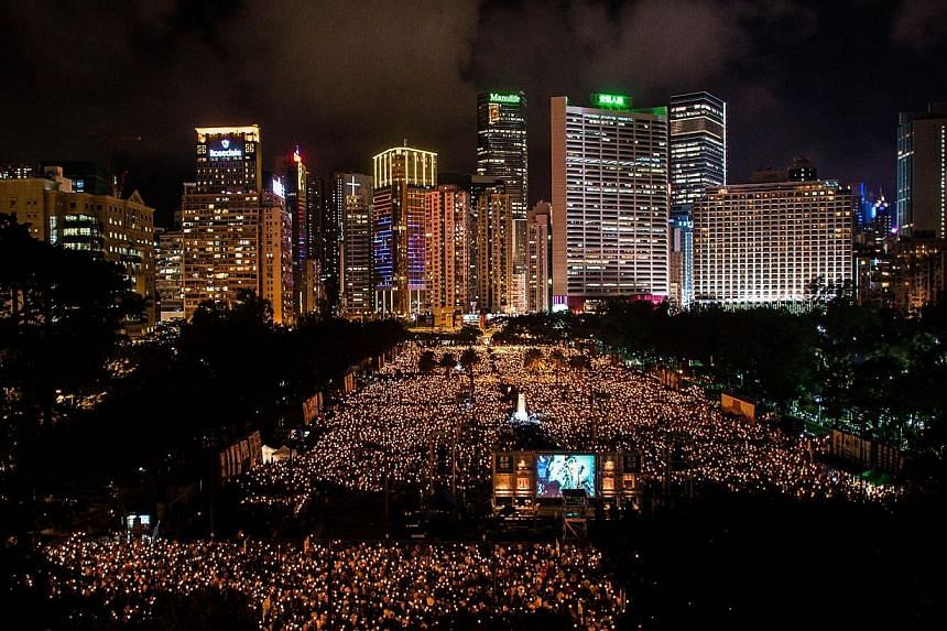 People hold candles to commemorate China's 1989 Tiananmen Square events during a candlelight vigil in Hong Kong on June 4, 2014. China's state censors on Thursday, June 5, 2014, scrubbed the Internet of references to commemorations of the Tianan