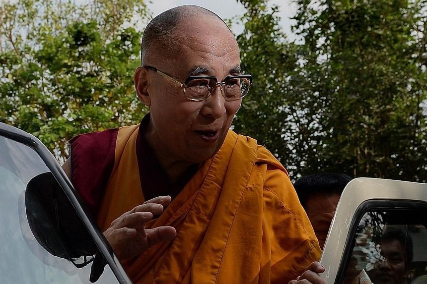 "The Dalai Lama waves to followers as he arrives to give a discourse on ""Introductory Teaching on Buddhism"" in Mumbai on on May 30, 2014. -- PHOTO: AFP"