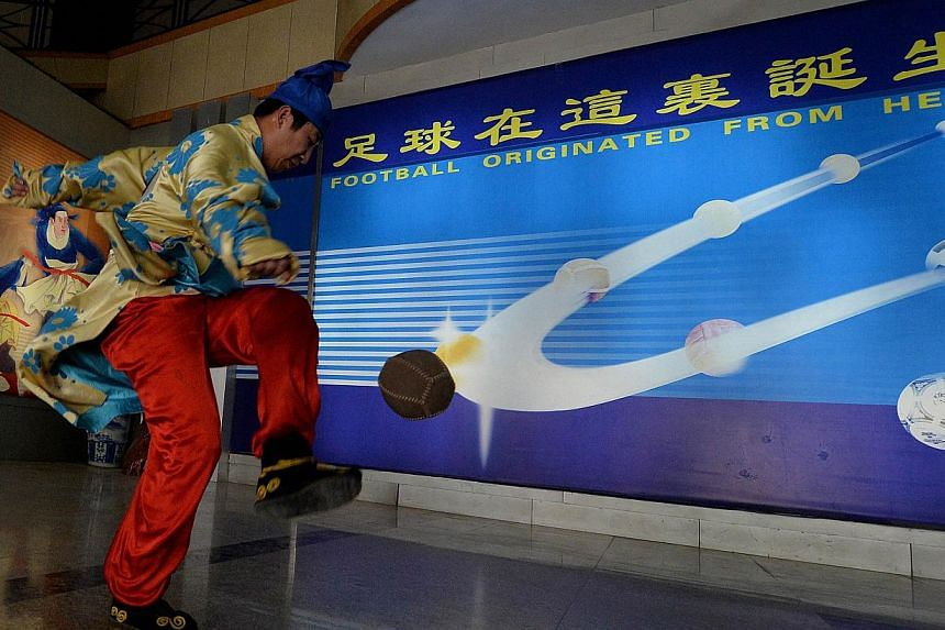 A traditional Chinese Cuju football player at the Linzi Football Museum in Zibo, Shandong Province on May 15, 2014. -- PHOTO: AFP