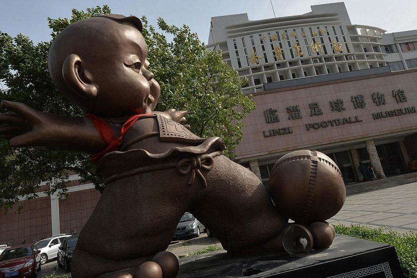 A statue of a caricatured traditional Chinese Cuju football player at the Linzi Football Museum in Zibo, Shandong Province on May 15, 2014. -- PHOTO: AFP