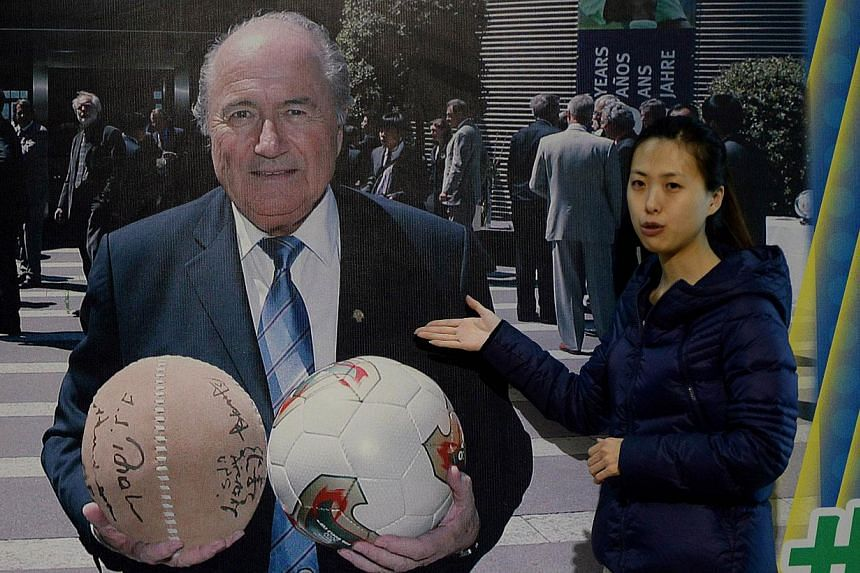 Fifa president Sepp Blatter holding a traditional Chinese Cuju ball (left) and a regular football at the Linzi Football Museum in Zibo, Shandong Province on May 15, 2014. -- PHOTO: AFP