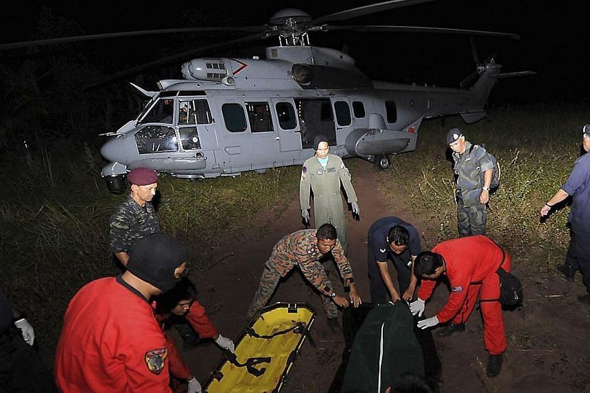 Search and rescue personnel prepare to load a body on to a Royal Malaysian Air Force helicopter during the search for missing British backpacker Gareth Huntley at Juara village on Tioman Island on June 4, 2014. -- PHOTO: REUTERS