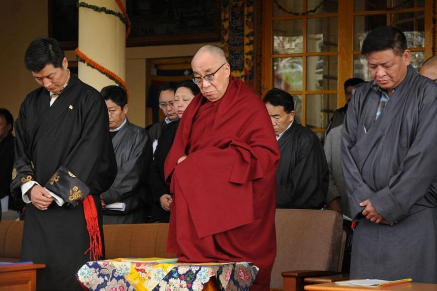 In this photograph taken on Mar 10, 2012, Tibetan spiritual leader the Dalai Lama (C), Kalon Tripa of the Central Tibetan Administration Lobsang Sangay (L), and Speaker of the Tibetan Parliament-in-exile Penpa Tsering (R) observe a minute of silence