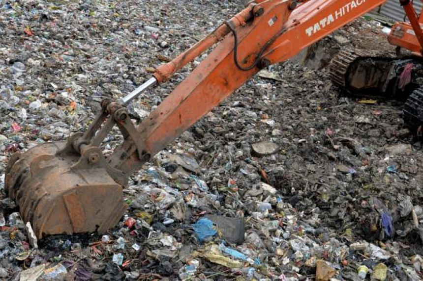 An excavator digs out waste, including discarded plastic packaging clogging a canal on the eve of World Environment Day in Bangalore on June 4, 2014. Some 265 million tonnes of plastic are produced globally each year, out of which 170 million are lar