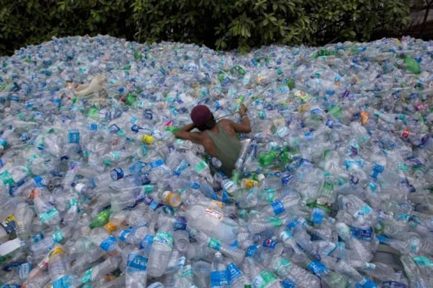 A worker uses a rope to move through a pile of empty plastic bottles at a recycling workshop in Mumbai on June 5, 2014. According to the United Nations Environment Programme website, World Environment Day is celebrated annually on June 5 to raise glo