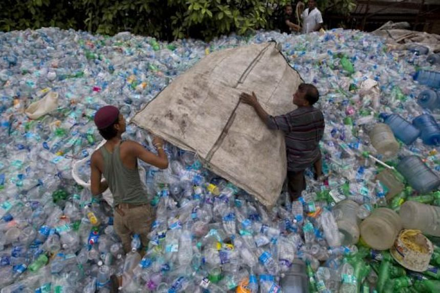 Workers empty a sack of plastic bottles at a recycling workshop in Mumbai on June 5, 2014. According to the United Nations Environment Programme website, World Environment Day is celebrated annually on June 5 to raise global awareness and motivate ac