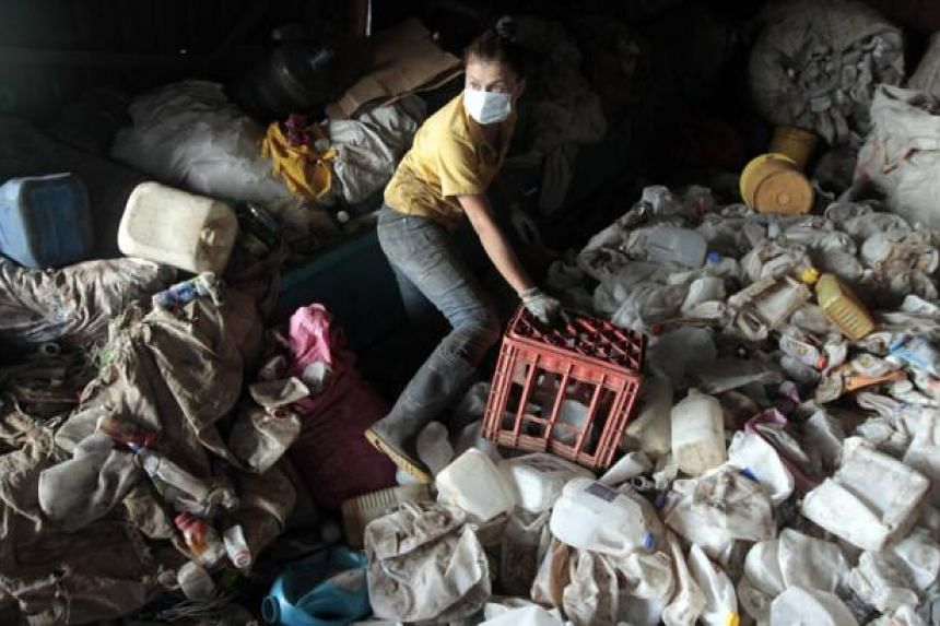 An employee collects plastic bottles at a garbage recycling centre in Managua on June 3, 2014. According to local media, Nicaragua plans to export and sell about US$40 million worth of scrap, waste paper, plastic and glass to countries such as Taiwan