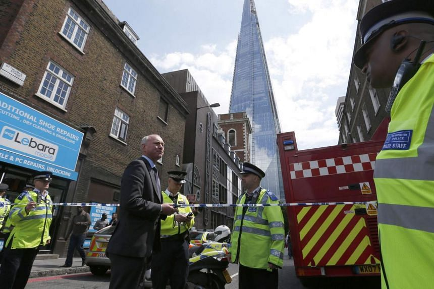 Police officers block streets near The Shard skyscaper in central London on June 5, 2014. London's tallest building, The Shard, was evacuated for several hours on Thursday, June 5, 2014 after smoke started billowing from the basement of the 87-s