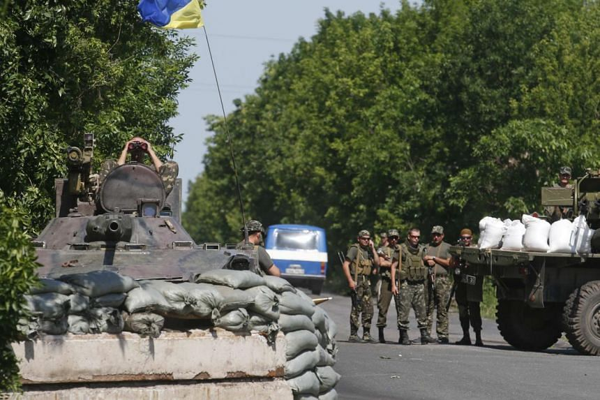 Ukrainian servicemen stand guard at a checkpoint near the town of Amvrosievka, in Donetsk region on June 5, 2014.Thousands of Ukrainians are flooding across the border into Russia to escape the armed conflict, Russian Prime Minister Dmitry Medv