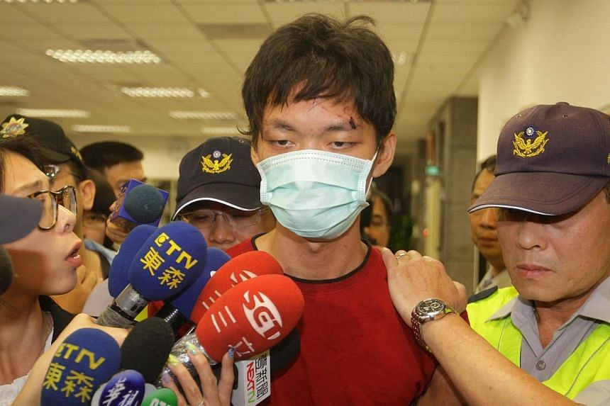 Cheng Chieh (centre) is transferred by policemen at a local police station in New Taipei City on May 22, 2014. The operator of Taiwan's subway system said on Thursday it was seeking compensation for operational losses from Cheng, who killed four peop