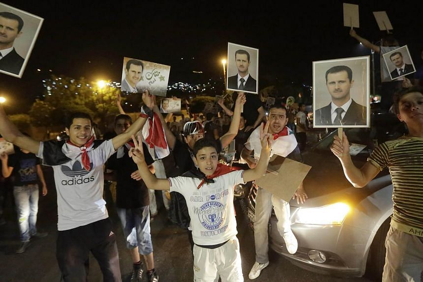 Syrians hold pictures of re-elected Syrian President Bashar al-Assad as they celebrate in Damascus after Mr Assad was announced as the winner of the country's presidential elections on June 4, 2014. -- PHOTO: AFP