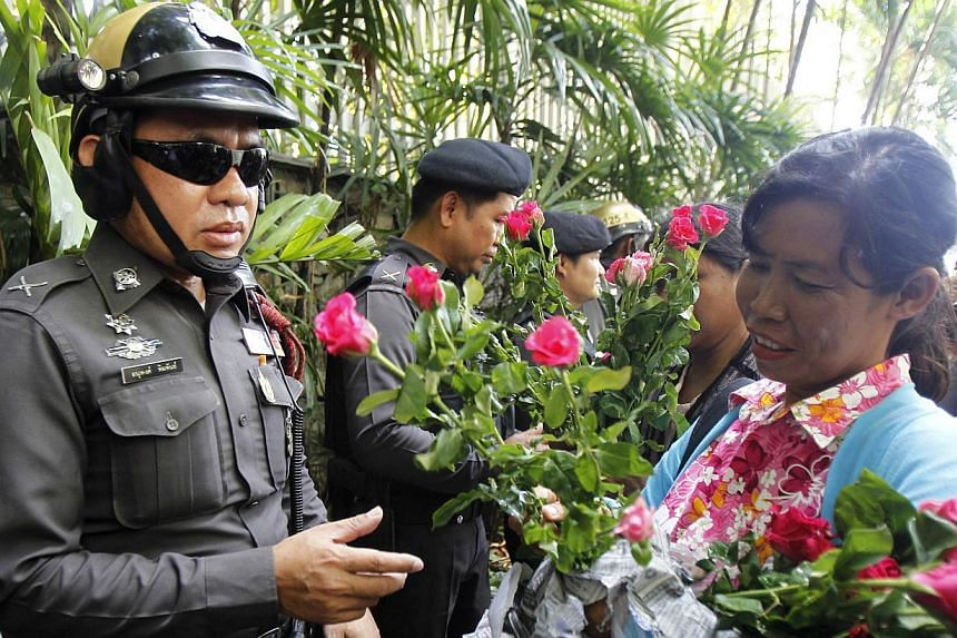 A military rule supporter hands roses to policemen guarding the Australian embassy in Bangkok June 4, 2014. -- PHOTO: REUTERS