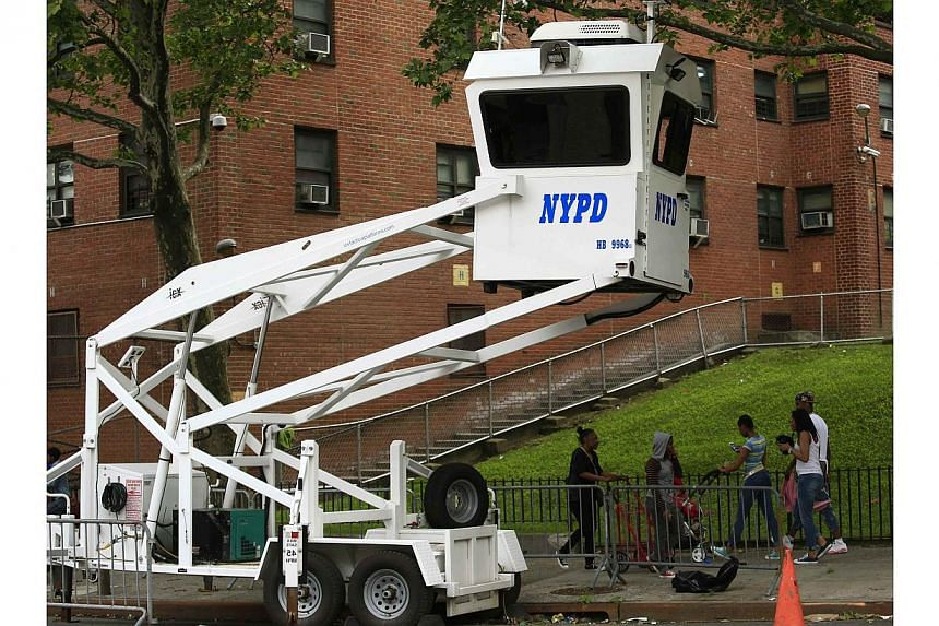 Passers-by walk next to a NYPD booth at the zone of the General Grant houses in New York on June 4, 2014. -- PHOTO: REUTERS