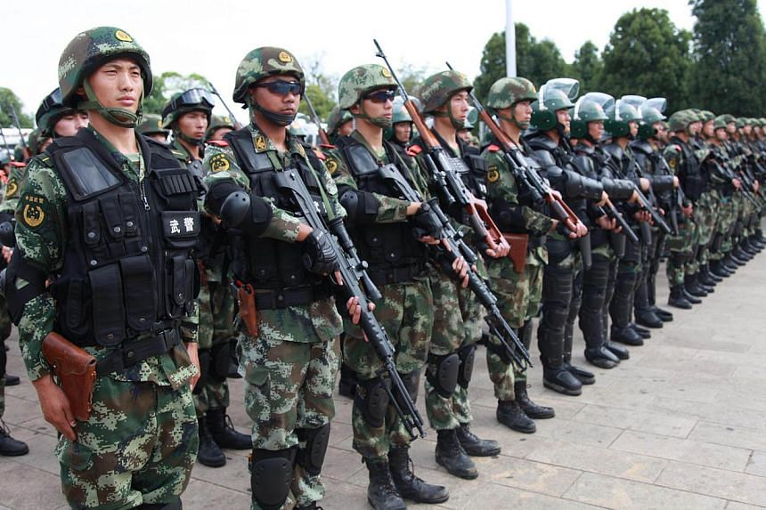 Paramilitary police attending a ceremony of an anti-terrorism campaign in Honghe, southwest China's Yunnan province on June 3, 2014. -- PHOTO: AFP
