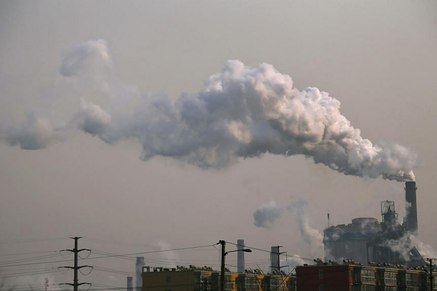 Smoke rises from a chimney of a steel plant next to residential buildings on a hazy day in Fengnan district of Tangshan, Hebei province on Feb 18, 2014. -- PHOTO: REUTERS