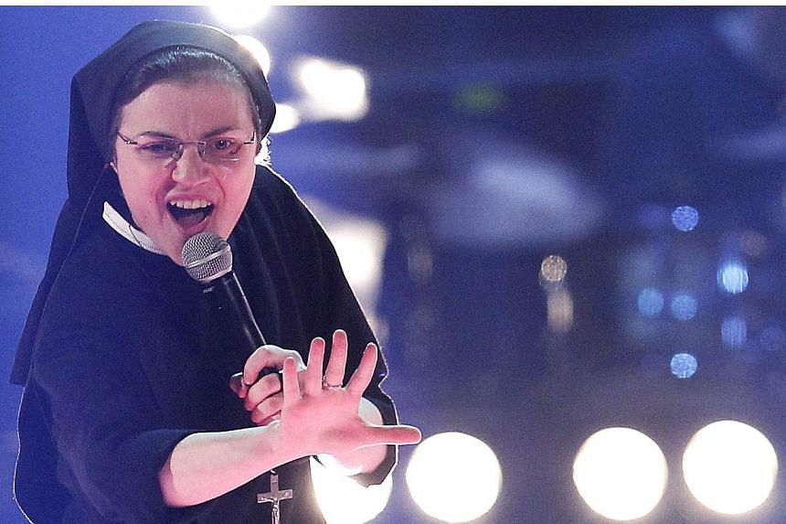 "Sister Cristina Scuccia performs during the Italian State RAI TV show final ""The Voice of Italy"" in Milan on June 5, 2014. The 25-year-old nun is already a talent show sensation thanks to her habit-clad performances but also has on her side the criti"