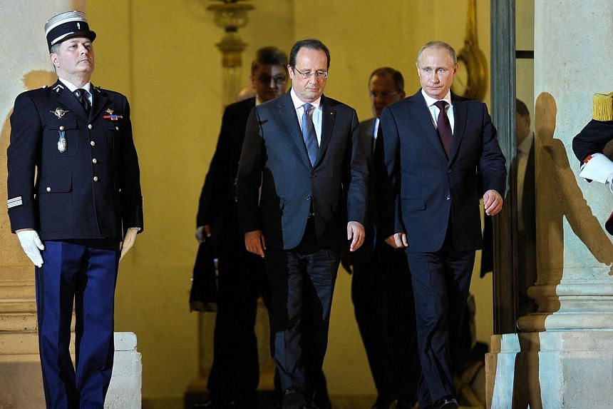 Russian President Vladimir Putin (right), escorted by French President Francois Hollande, leaves the Elysee palace following their meeting and dinner in Paris on June 5, 2014. Russian President Vladimir Putin met for talks with French President Franc