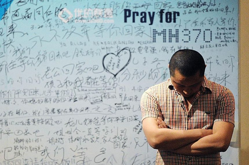 A man stands in front of a billboard in support of missing Malaysia Airlines flight MH370 as Chinese relatives of passengers on the missing Malaysia Airlines flight MH370 have a meeting at the Metro Park Hotel in Beijing on April 23, 2014.It is