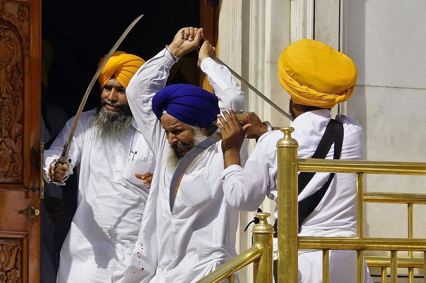 Sikhs wield swords during their clash inside the complex of the holy Sikh shrine, the Golden Temple, in the northern Indian city of Amritsar on June 6, 2014. -- PHOTO: AFP