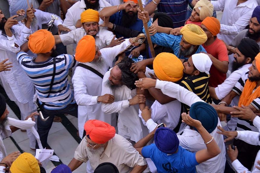 Sikh activists clash with members of the Shiromani Gurudwara Prabhandak Committee ( SGPC) during commemorations for the 30th Anniversary of Operation Blue Star at the Golden Temple in Amritsar on June 6, 2014. -- PHOTO: AFP