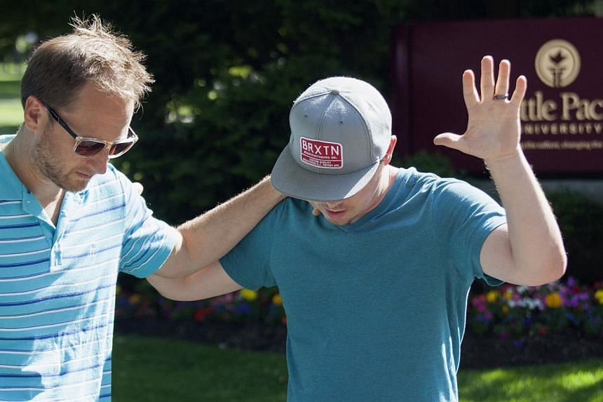 Local pastor Tim Gaydos (left) prays with Chris Holt, a Seattle Pacific University alumnus, at Seattle Pacific University after the campus was evacuated due to a shooting in Seattle, Washington on June 5, 2014. A gunman opened fire on Thursday on the