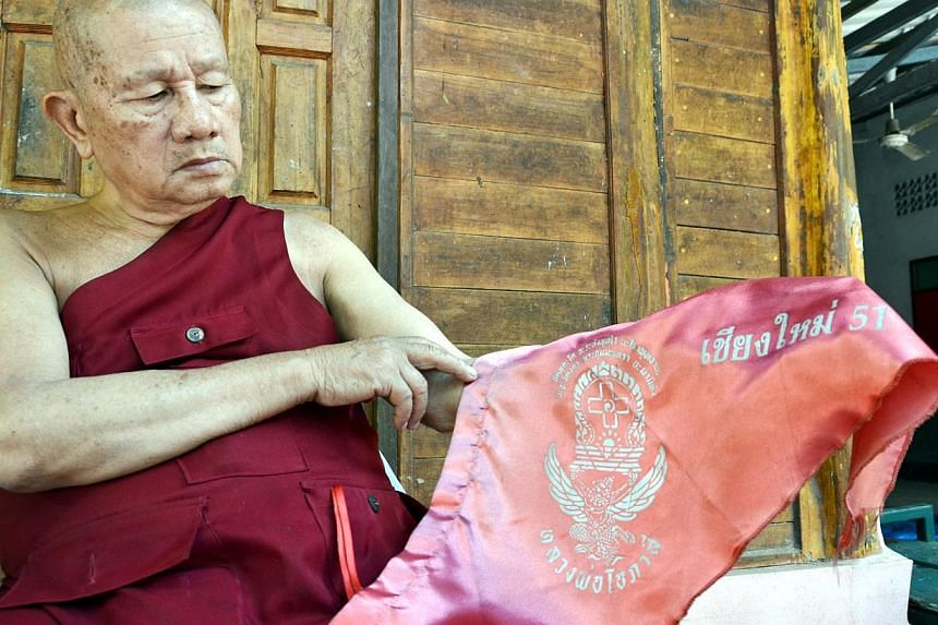 Phra Khru Suthep Sitthikun, the abbot of a temple in Chiang Mai, with the flags that authorities removed from his temple wall because they deemed it a symbol of the red shirts. The red shirts are key supporters of the ousted government. -- ST PHOTO: