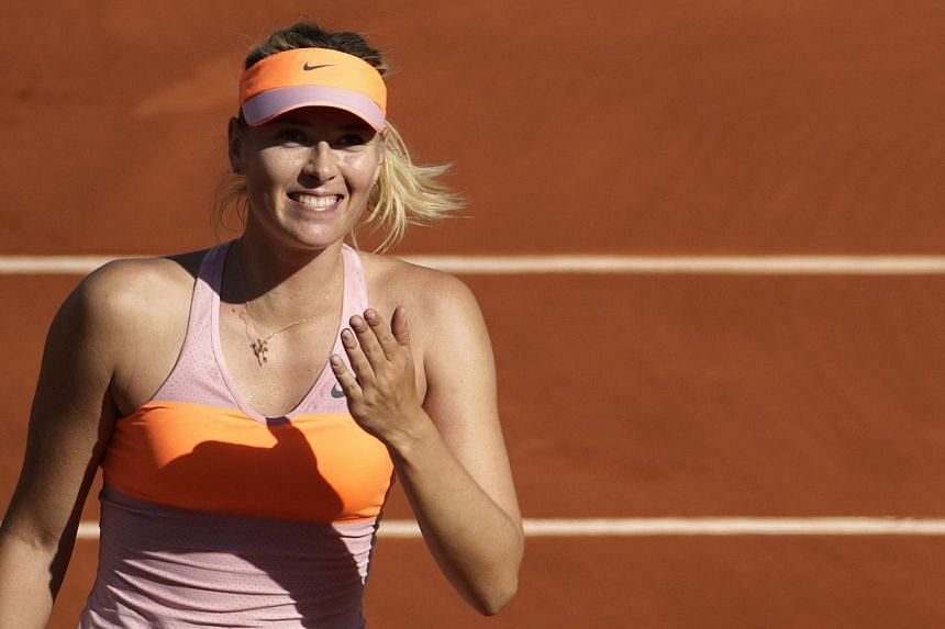 Russia's Maria Sharapova celebrates her victory over Canada's Eugenie Bouchard at the end of her French tennis Open semi-final match against at the Roland Garros stadium in Paris on June 5, 2014. -- PHOTO: AFP