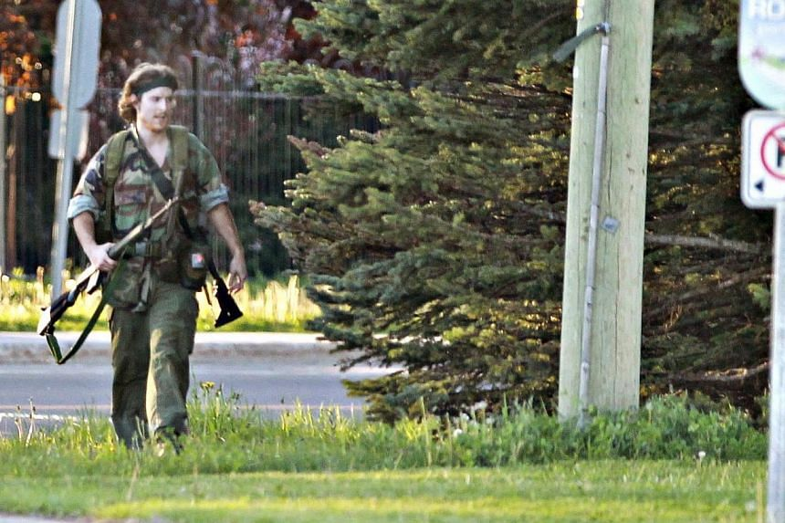 A heavily armed man that police have identified as Justin Bourque walks on Hildegard Drive in Moncton, New Brunswick on June 4, 2014 after several shots were fired in the area. Canadian police said on Friday, June 6, 2014, they had arrested the